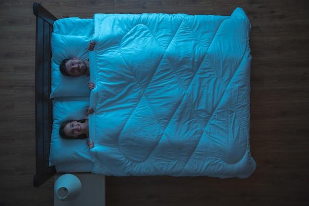 Улыбающаяся пара лежала на кровати. вечер ночное время. вид сверху