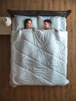 Улыбающаяся пара лежала на кровати. вид сверху
