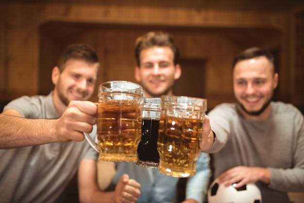 미소 행복한 친구들은 맥주와 함께 잔을 부딪친다