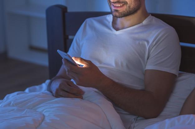 웃는 남자는 침대에 전화기를 들고 앉아 있다. 밤 시간