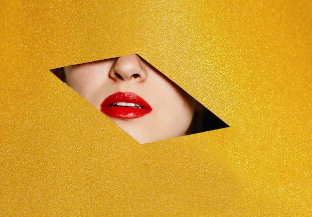 ふっくらした赤い唇を持つ美しい少女の笑顔は、黄色のきらびやかな紙の穴をのぞきます。ファッションの概念、美容、メイク、化粧品。
