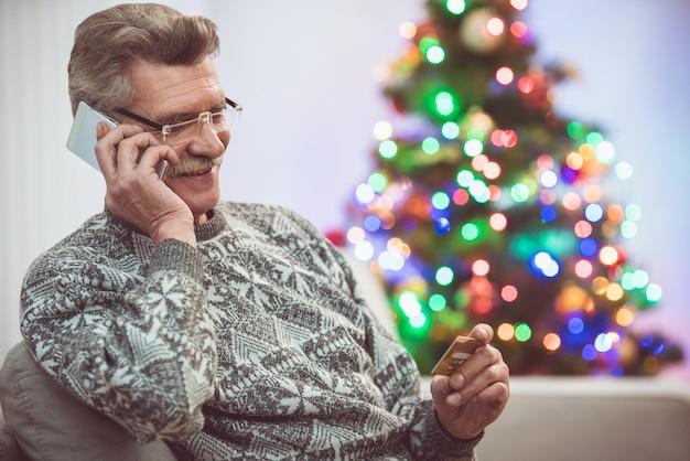 Улыбающийся старик с телефоном кредитной карты возле елки