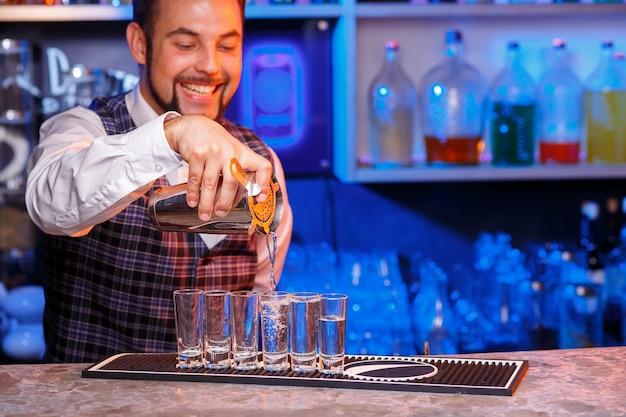 仕事中の笑顔のバーテンダー、彼はカクテルを準備しています。サービスと飲み物についての概念。