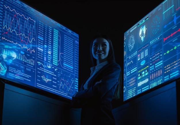 어두운 사무실에서 파란색 모니터 사이에 서 있는 웃는 비즈니스 여성
