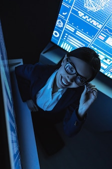 웃는 비즈니스 여성은 어두운 사무실에서 센서 모니터와 함께 작동합니다.