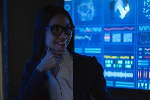 어두운 사무실에 서 있는 웃는 비즈니스 우먼