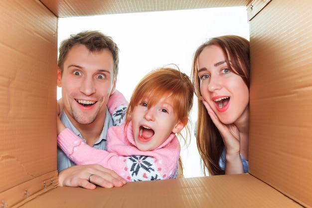 引っ越しの準備ができている段ボール箱の笑顔の家族