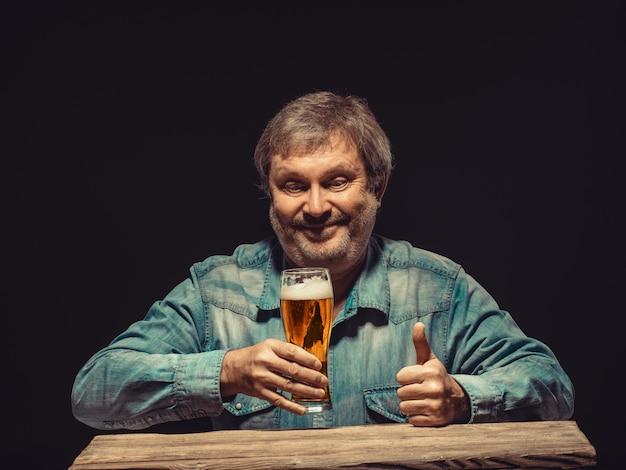 Улыбающийся человек в джинсовой рубашке с бокалом пива