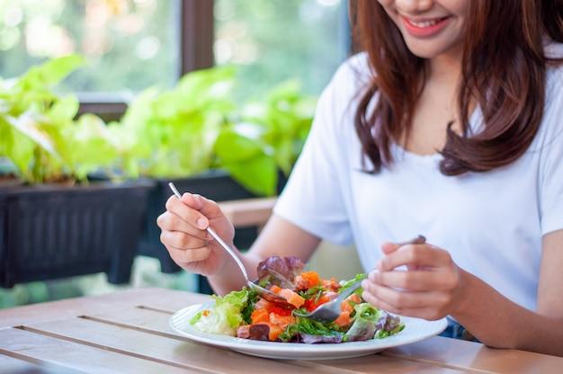 笑顔の女性は、サーモンサラダを食べることを楽しんでいます。体重とダイエットを減らすには、体に有益な食品を食べます。減量のコンセプトです。