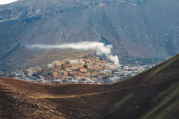 山の村の上の煙。コーカサス山脈の高台にある小さな村チョー。ダゲスタン、ロシア。