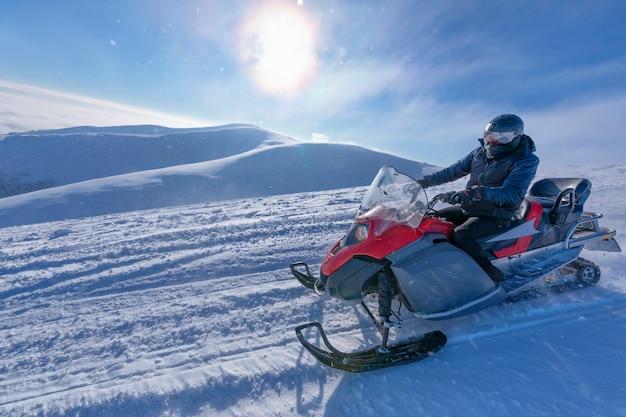Снегоход движется по склону заснеженной горы.