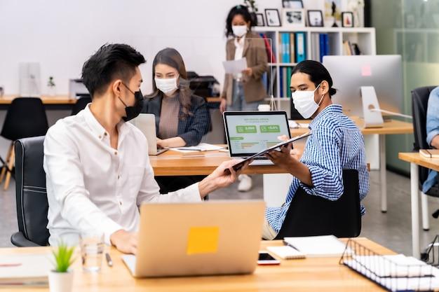 Социальная дистанция в офисе с деловой командой в масках для лица