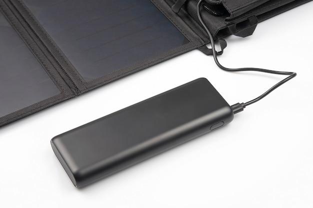 Солнечная панель заряжает аккумулятор пауэрбанка для смартфона по белому. цифровые технологии и устройства