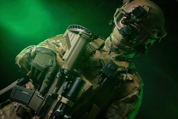 야간 투시경과 어두운 배경을 가진 군복을 입은 군인