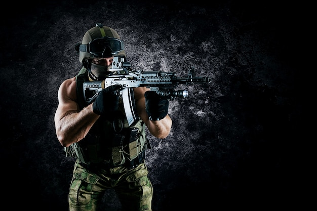 Боец спецподразделения целится в коллиматорный прицел своего пулемета. смешанная техника
