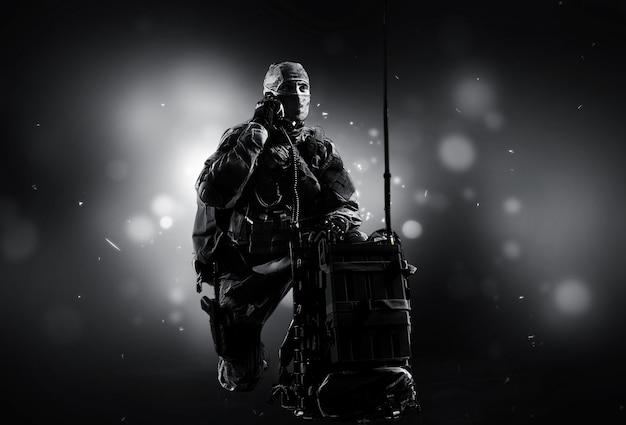 군복을 입은 특수부대의 병사가 위성통신기기의 근처에 앉아 지원을 하고 있다. 혼합 매체