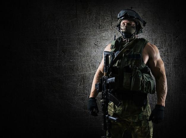 Военнослужащий спецподразделения находится на инструктаже в полной экипировке и слушает задание. смешанная техника