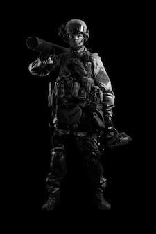 Солдат спецподразделения стоит в военной форме с тараном на плече и устройством для открывания дверей. смешанная техника