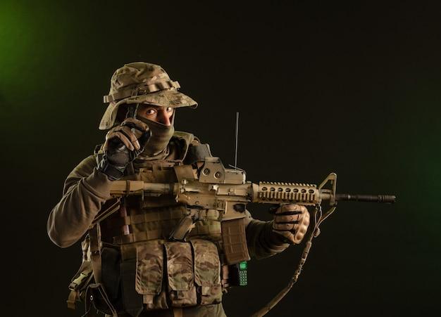 暗い背景に武器を持った軍服を着た兵士妨害工作員