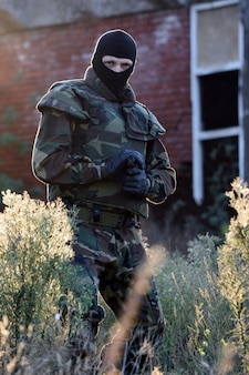 Солдат с ружьем на природе гуляет.