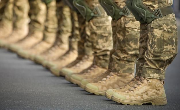 На ногах солдаты одеты в ботильоны и камуфляжные штаны.