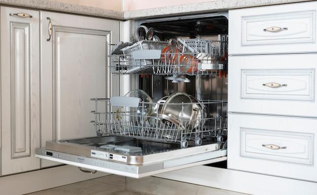 Некоторая грязная посуда на подносе в посудомоечной машине в кухне.