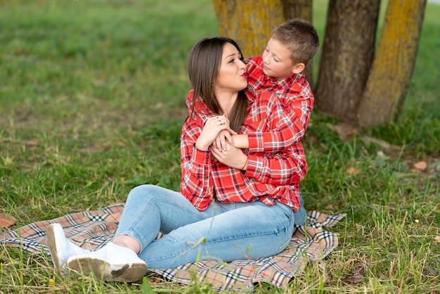 息子は市松模様のベッドカバーに座っているお母さんの肩を優しく抱きしめます。あらゆる目的のために。