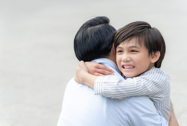 息子は彼の父を抱きしめて幸せな、独身のお父さんと息子の幸せアジアの家族の概念を満たします