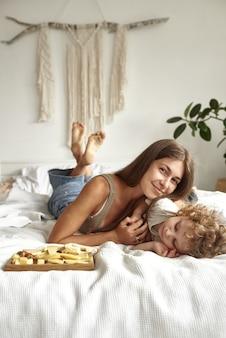 아들은 침대에 누워 자신이 가장 좋아하는 치즈를 먹습니다.