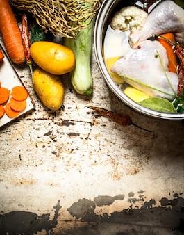 鶏肉、野菜、スパイスのスープ。素朴な背景に。