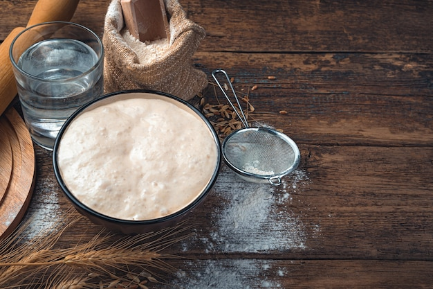 빵 사워 도우가 활동적입니다. 빵을 만들기위한 재료. 복사 할 공간이있는 요리 배경.