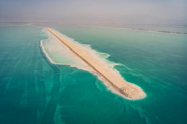 사해의 남쪽 부분은 미네랄을 추출하는 웅덩이로 나뉩니다. 바위가 많은 해안은 사해의 푸른 바닷물에 씻겨진 하얀 소금 결정으로 덮여 있습니다.