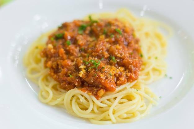 Спагетти с говяжьим соусом, в состав которого входят говяжий лук и помидоры. налит говяжий соус.