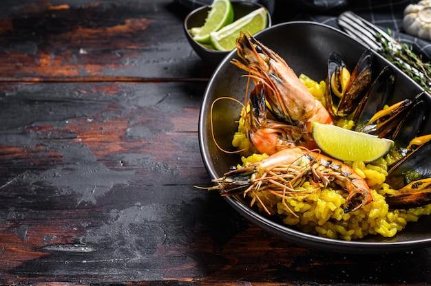 Испанская паэлья из морепродуктов с креветками, креветками, осьминогами и мидиями. черный деревянный фон. вид сверху. скопируйте пространство.