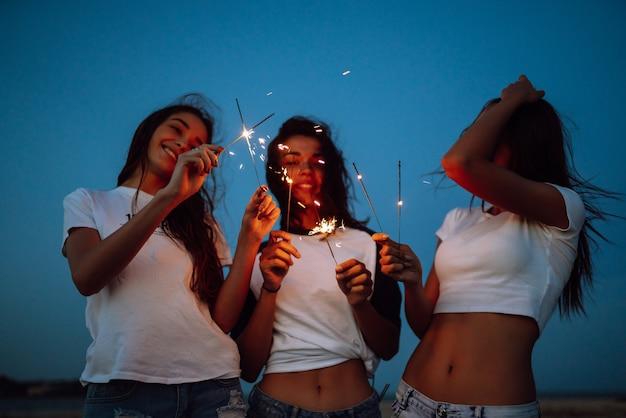 ビーチで若い女の子の手に花火。花火とビーチでパーティーを楽しんでいる3人の女の子。夏の休日、休暇、リラックス、ライフスタイルのコンセプト。