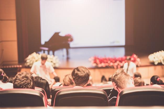 ビジネス会議について話すスピーカー。会議ホールでの観客。