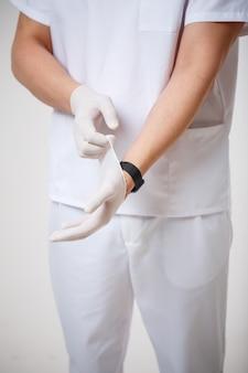 전문의는 시술 전 손에 고무장갑을 끼고 있습니다. 세균으로부터 보호하는 라텍스 장갑