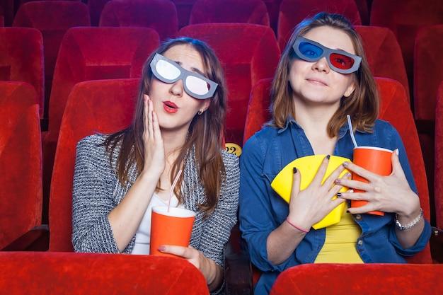 Зрители сидят в кинотеатре и смотрят фильм с чашками попкорна.