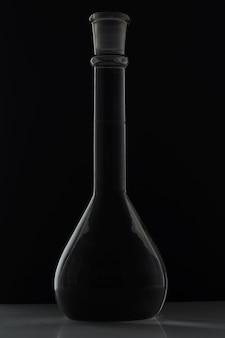 黒の背景に長いくちばしを持つ液体で満たされた球形フラスコ