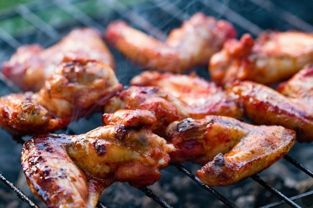Острые маринованные куриные крылышки на гриле на летнем барбекю с раскаленным пламенем, крупным планом