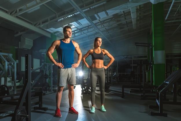 スポーツカップルは明るい光の背景にジムに立っています