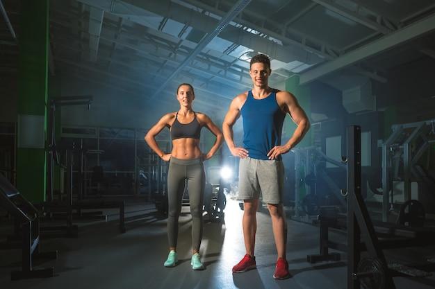 スポーツカップルは明るい光の背景にモダンなジムに立っています