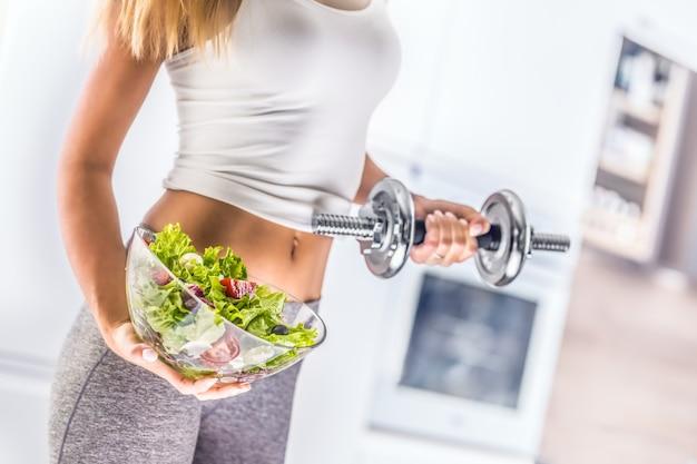 Спортивная фигура привлекательной женщины, держащей миску из свежего овощного салата и гантелей.