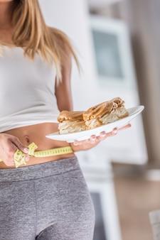 고칼로리 케이크와 측정 테이프가 있는 접시를 들고 있는 매력적인 여성의 스포츠 그림.
