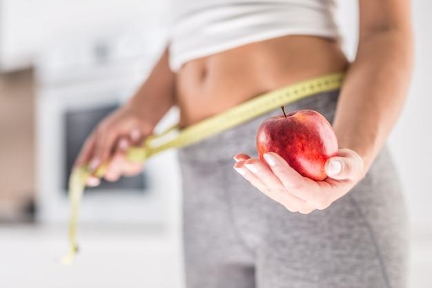 赤いリンゴとメジャーテープを持っている魅力的な女性のスポーツフィギュア。