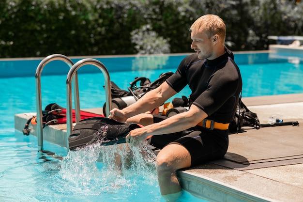 스포츠 남자는 수영장에서 수영하기 전에 지느러미를 걸어서