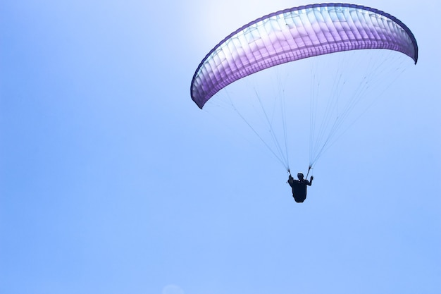Спортсмен, летящий на параплане в голубом небе