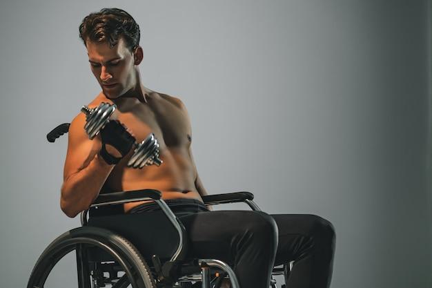 Спортсмен в инвалидной коляске работает с гантелями
