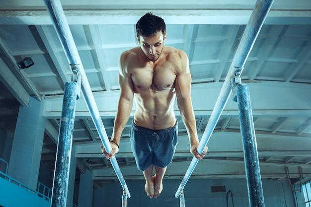 체육관에서 어려운 체조 운동을 하는 스포츠맨. 스포츠, 운동, 체조 선수, 건강, 훈련, 운동 선수 개념. 백인 적합 모델