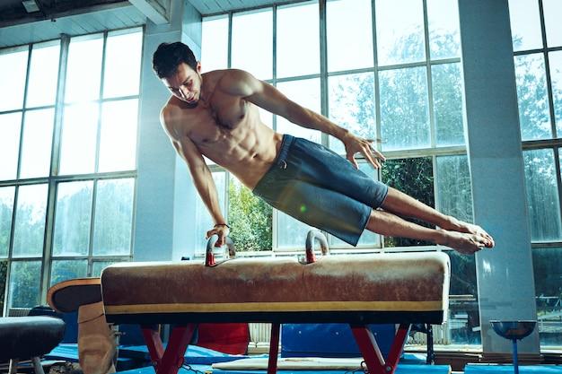 체육관에서 어려운 체조 운동을 하는 스포츠맨 스포츠 운동 체조 선수
